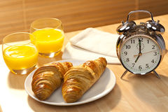 Breakfast Croissant, Orange Juice and Alarm Clock. A healthy continental breakfast of croissant pastries, orange juice, oranges Illuminated with golden early Stock Photo