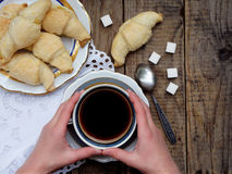 Breakfast with croissants and black coffee composition with girl hand on wooden retro background. Stock Image