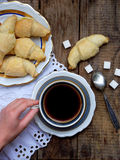 Breakfast with croissants and black coffee composition with girl hand on wooden retro background. Stock Photography