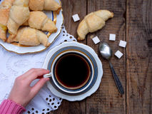 Breakfast with croissants and black coffee composition with girl hand on wooden retro background. Royalty Free Stock Images