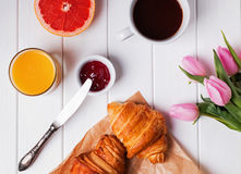 Breakfast with croissants and coffee and pink tulips on the whit Royalty Free Stock Images