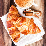Breakfast with Croissants and Coffee on wooden rustic background Stock Photos