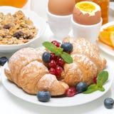 Breakfast with croissants, eggs, muesli, fresh berries, oranges Stock Images
