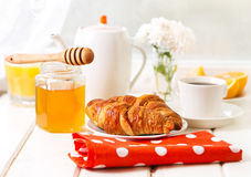 Breakfast with croissants, honey and coffee. On wooden table Royalty Free Stock Photography