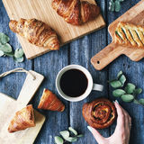 Breakfast with croissants, leaves, cutting board and black coffee composition with girl hand on wooden retro background. Flat lay, top view Stock Photos