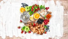 Breakfast with croissants, muesli, fresh berries, fruits. Health. Breakfast with fresh berries, fruits orange, apple, milkcroissants, muesli. Healthy food royalty free stock image