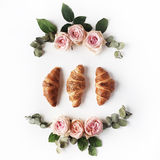 Breakfast with croissants, pink rose flower, petals composition. Flat lay, top view royalty free stock photography