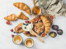 Breakfast with croissants, ricotta, coffee and berries over marble background. Breakfast with croissants, homemade ricotta cheese, figs, fresh berries Royalty Free Stock Image