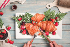 Breakfast with croissants and strawberry on blue wooden table. View from above Royalty Free Stock Photos