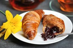 Breakfast with croissants - tea, croissants, Lily on Royalty Free Stock Photo