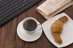 Breakfast with cup of black coffee, croissants and keyboard Stock Image