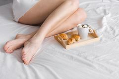 Breakfast in bed with cup of black coffee and croissants for woman royalty free stock photo