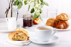 Breakfast - cup of coffee, croissants, jam and fruits on white table stock images