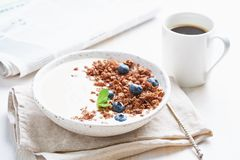 Breakfast with cup of coffee, newspaper, yogurt with chocolate granola, bilberry on a white background, side view. Breakfast with cup of coffee, newspaper stock photography
