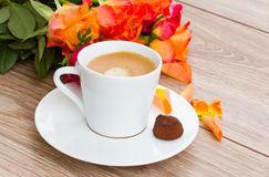 Cup of coffee with orange roses Royalty Free Stock Photos