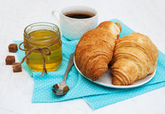 Breakfast. Cup of tea, croissants and honey on an old white table Royalty Free Stock Image