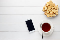 Breakfast of cup of tea and homemade heart shaped cookies and smartphone on white wooden table. Royalty Free Stock Photo