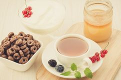 breakfast with a cup of tea, honey, in flakes, yogurt and berries/breakfast with a cup of tea, honey, in flakes, yogurt and royalty free stock photo