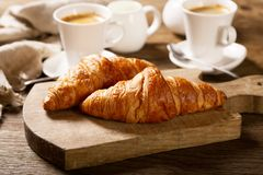 Breakfast with cups of coffee and croissants royalty free stock photos