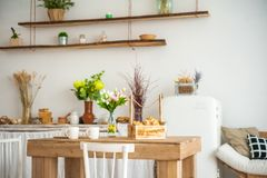 Breakfast cups and fruit. Spring tulips on the table. Wooden table in a bright rustic-style kitchen. Scandinavian style in the int royalty free stock images