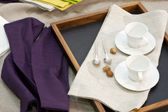 Breakfast cups on a tray. Two white coffee cups on a tray, with linen table napkins stock images