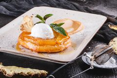 Breakfast with delicious apple strudel with pineapple, jam, ice cream garnished with mint and powdered sugar on light plate. Over dark background. Puff pastries stock photos