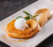 Breakfast with delicious apple strudel with pineapple, jam, ice cream garnished with mint and powdered sugar on light plate. Over dark background. Puff pastries royalty free stock photography