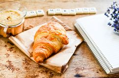 Breakfast. Delicious home made croissant,coffee ,notebook  and   fresh lavender  on wooden background. and good morning  written from scruble letters Royalty Free Stock Photos