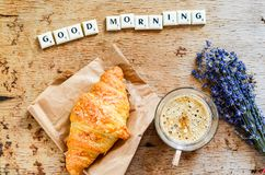 Breakfast. Delicious home made croissant,coffee ,notebook  and   fresh lavender  on wooden background. and good morning  written from scruble letters Royalty Free Stock Photo