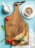 Breakfast or dessert set. Freshly baked croissants with strawberries, cup of coffee and milk in creamer on brown wooden Stock Photos