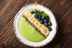Breakfast Detox Green Smoothie. Bowl from banana and spinach on wooden background. Healthy food concept with copy space, top view stock photos