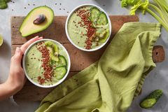 Breakfast Detox Green Smoothie From Kivi And Cucumber In The Bowl In Woman`s Hand On Wooden Board Stock Photo