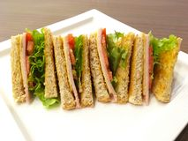 Sandwich wholewheat bread on white plate. Breakfast diet food. Sandwich wholewheat bread with lettuce, ham and yellow cheese on white plate over wooden table in Royalty Free Stock Images