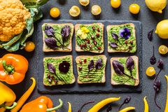 Breakfast different avocado sandwich. Different Fresh colorful organic vegetables. healthy raw vegan food on grey. Background Stock Photo