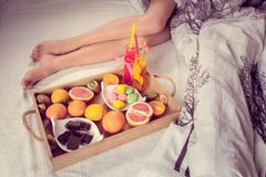 Breakfast from fruits to bed and female legs Stock Images
