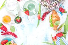 Breakfast or dining table with various delicacies for the holiday. Fresh strawberries and currants with soft cheese and red spring. Tulips. Coffee mugs on the stock images