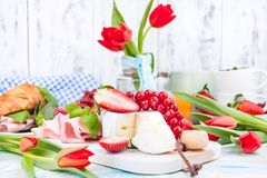 Breakfast or a dinner table with various delicacies for Easter meals. Fresh strawberries and currants with soft cheese and red. Spring tulips. Drinks and snacks stock image