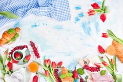 Breakfast or a dinner table with various delicacies for Easter meals. Fresh strawberries and currants with soft cheese and red. Spring tulips. Drinks and snacks royalty free stock image
