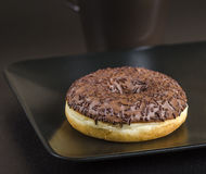 The breakfast Donut. A fresh baked  chocolate donut prepared for breakfast with a coffee cup in the background Stock Photography