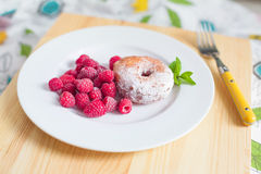 Breakfast. Donut with raspberries on plate Stock Images