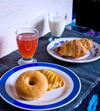 Breakfast with donuts, salty croissant, fruit juice and milk Royalty Free Stock Photos