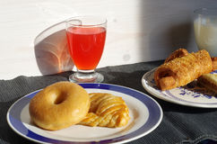 Breakfast with donuts, salty croissant, fruit juice and milk stock image
