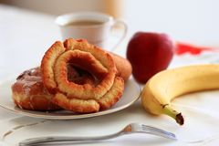 Breakfast doughnuts with Coffee. And fruit showing a doughnut and cinnamon bun Royalty Free Stock Images