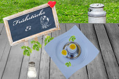 Breakfast egg and board with inscription. Egg with plates and salt shaker on a wooden board, board with inscription Stock Image