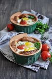 For breakfast, egg with bread and whole tomatoes cherry baked in oven molds Stock Photography