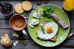 Breakfast with an egg on a toast. Breakfast with an egg and toast on a wooden table Royalty Free Stock Image