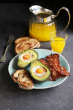 Breakfast with eggs baked in avocado and bacon Stock Image