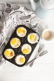 Breakfast eggs baked in cake mold with ground parmesan Stock Photos