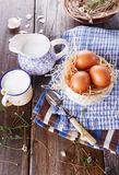 Breakfast with eggs on blue kitchen towels. Brown chicken eggs in straw basket served for breakfast with rustic metal cup of milk, blue pitcher and vintage spoon royalty free stock photography