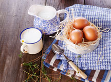Breakfast with eggs on blue kitchen towels. Brown chicken eggs in straw basket served for breakfast with rustic metal cup of milk, blue pitcher and vintage spoon stock photo